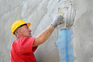 Wall insulation, mason, worker spreading mortar over mesh