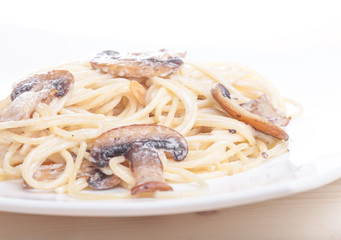 pasta topped with mushrooms on white background