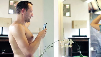 Shirtless man taking photo of himself in the bathroom