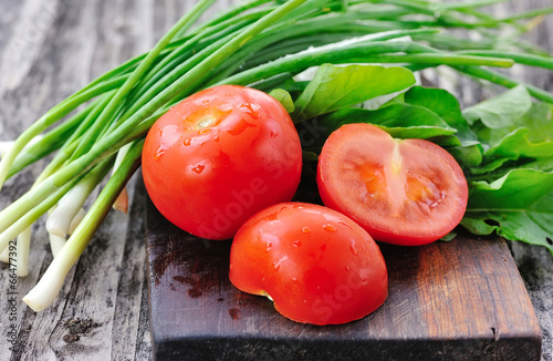 Tomatoes with onions and arugula on a wooden board