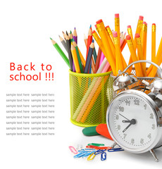 Alarm clock and school accessories on a white background.