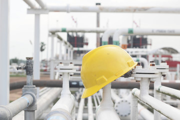 yellow hard hat on pipe line