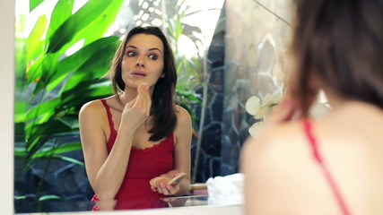 Woman applying makeup, powder on her face in front of the mirror