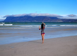 Girl walking on the Sunrise beach in Cape Town.