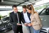 Fototapety Couple in car dealership looking at brochure with salesman