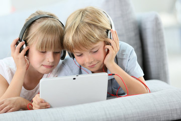 Kids listening to music on internet with tablet
