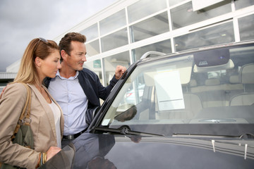 Couple in car dealership looking at information on windshield