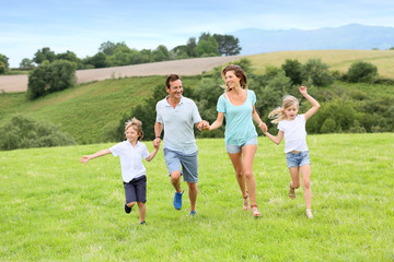Happy family running in countryside