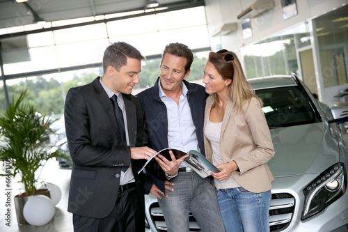 Couple in car dealership looking at brochure with salesman - 66481305