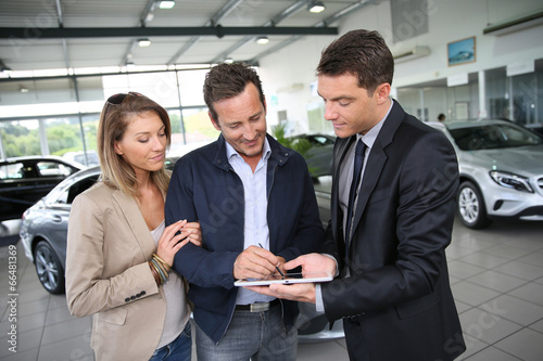 Couple signing car purchase order on digital tablet - 66481369