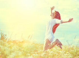Beauty model girl in white dress jumping on summer field