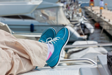 Legs in pants and bright blue topsiders on yacht
