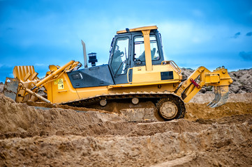 bulldozer or excavator working with soil on construction site