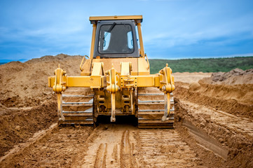 Bulldozer with steel blade moving soil and sand around