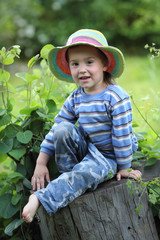 boy in rainbow hat in the garden