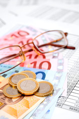 Glasses, euro and coins on documents.