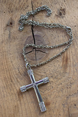 Silver christian cross necklace with  diamonds on wooden backgro