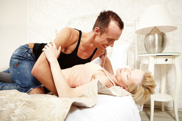 Lovely couple enjoying love touches in bedroom