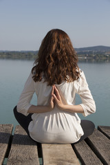 Woman meditating in reverse namaste pose during yoga by lake