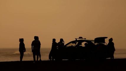 Freunde am Strand im Sonnenuntergang