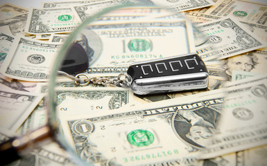 Key from the car and a magnifier on dollars.