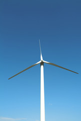 Wind turbine against sky, blue background