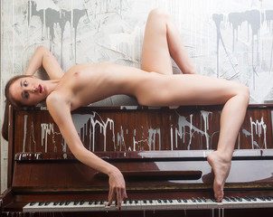 beautiful naked woman poses on piano