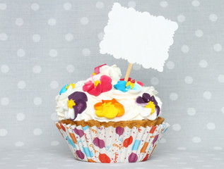 Cupcake with blank card on vintage retro background.