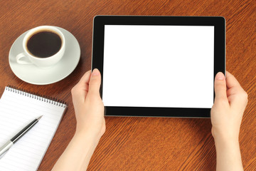 Hands hold tablet PC on wooden background .