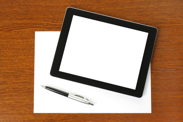 Tablet PC, paper and pen on wooden background .