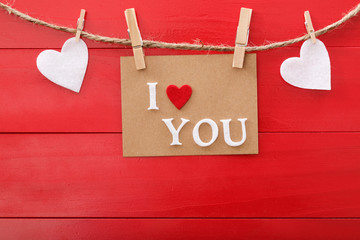 I Love You message card over red wooden board