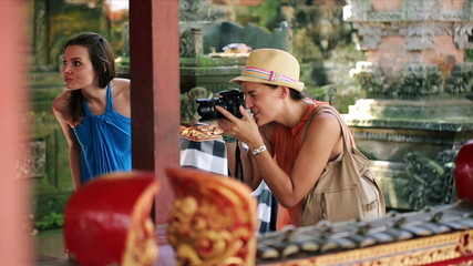 Girlfriends, tourist taking photos in ancient Bali temple