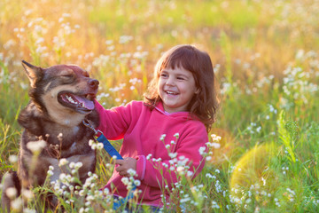 Happy little girl with big dog sitting in the lawn