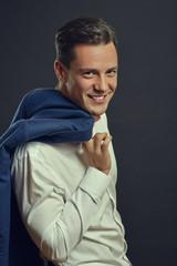 Cheerful handsome businessman holding blue jacket over shoulder