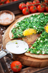 Pizza with herbs and eggs, selective focus