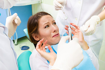 Female patient in dentist office scared, afraid of doctor