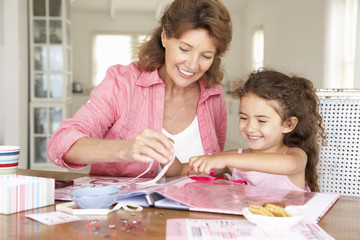 Senior woman scrapbooking with granddaughter