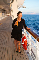 Happy woman stands on cruise liner deck and holds a cocktail