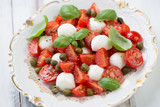 Salad with cherry tomatoes, mozzarella, capers and green basil