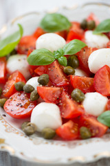 Caprese salad on a glass plate, close-up, vertical shot