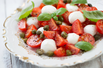 Caprese salad with capers, close-up, studio shot