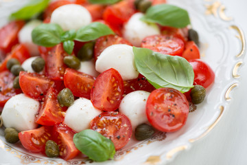 Glass plate with caprese salad, horizontal shot
