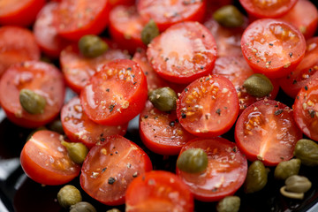 Cherry tomatoes with capers, sea salt and black pepper, close-up