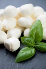 Mozzarella balls and green basil leaves, vertical shot