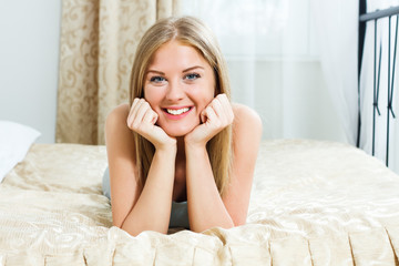 Beautiful blonde woman lying on bed