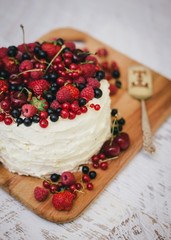 Cake with fresh berries and white glaze in woman's hands