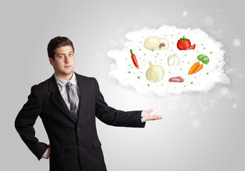 Handsome man presenting a cloud of healthy nutritional vegetable