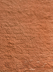 Texture of the red rough plastered wall