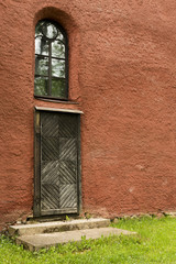 The red rough plastered wall with a door and a window