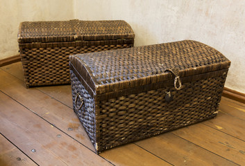 Two old wicker from cane chests standing in the room corner